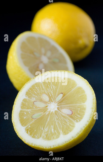 A fresh sliced organic Lemon with a defocused whole fruit in the background against black - Stock Image