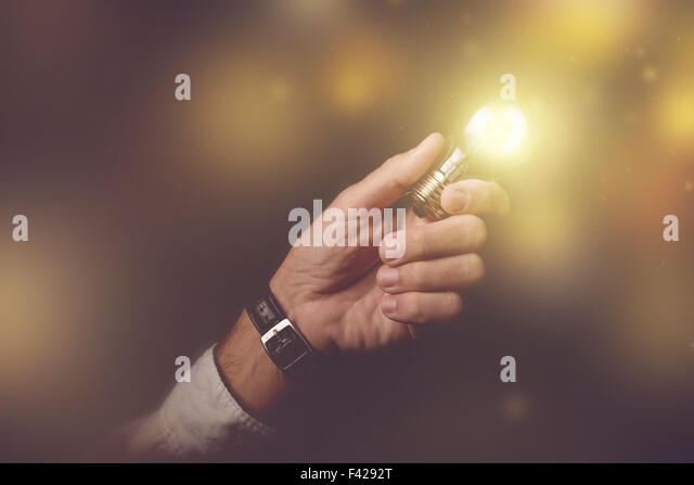 Big business idea visual metaphor, businessman with light bulb lightning up the dark office interior, retro toned - Stock Image