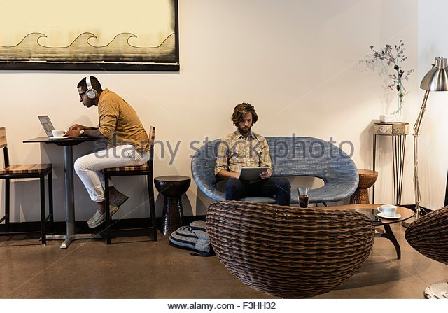 Two men in coffee shop using laptop and digital tablet - Stock Image