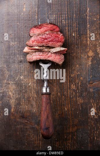 Slices of beef steak on meat fork on wooden background - Stock Image