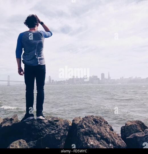 Man On Rocks Looking At Distant City - Stock Image