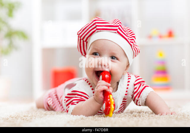 Cute baby in hat on the carpet having fun - Stock Image