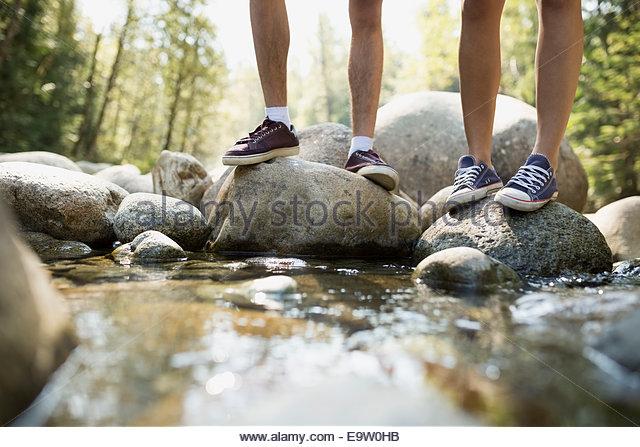 Friends standing on rocks in creek - Stock Image