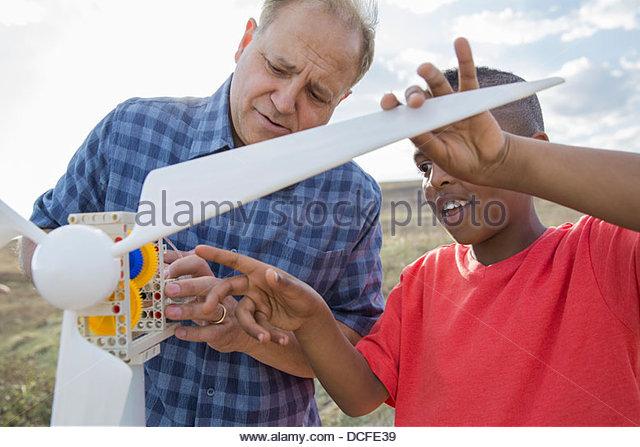 Man explaining wind turbine to schoolboy - Stock Image