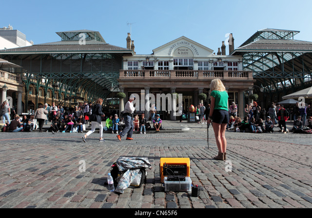 Entertainer performs with two female tourists in Londons Covent Garden Square - Stock Image