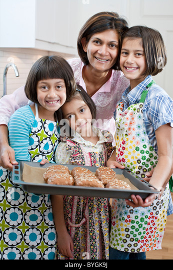 Portrait of mother with three daughters with freshly made rolls - Stock-Bilder
