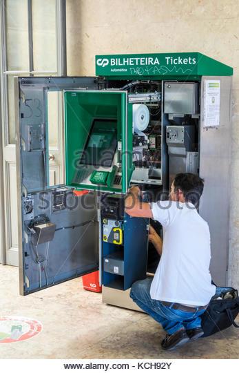 Lisbon Portugal Santa Apolonia Comboios de Portugal railway train station vending machine tickets technician repairman - Stock Image