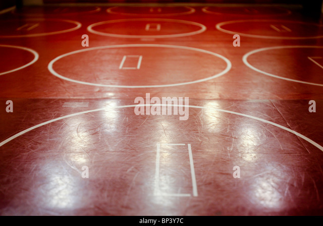 Well worn red school wrestling mat in a gym. - Stock Image