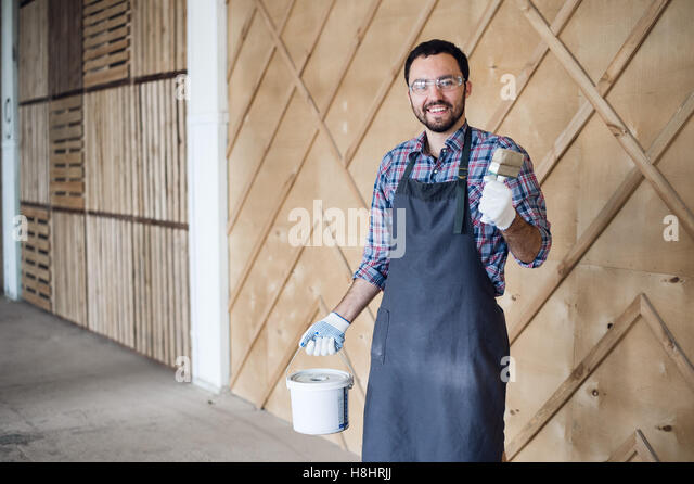 young painter man with tin of painting and brush showing thumbs up - Stock Image