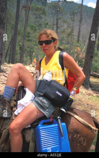 pico duarte hiking woman dismounting mule Dominican Republic Bermudez National Park trek trekking trail hiking adventure - Stock Image