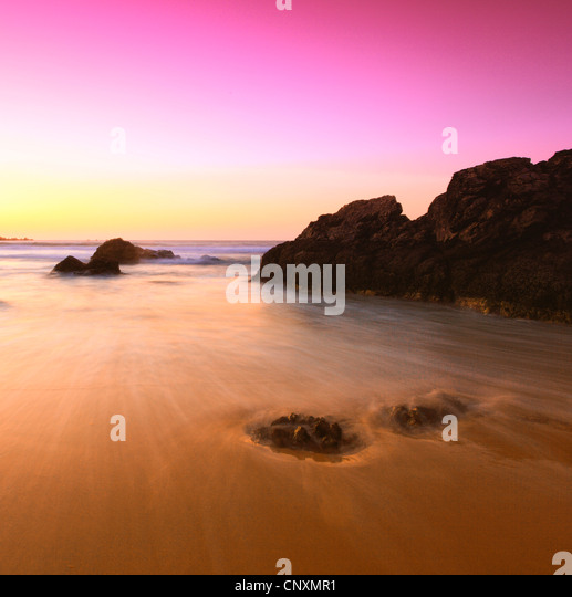 coastal rock at sandy beach in evening light, United Kingdom, Scotland - Stock Image