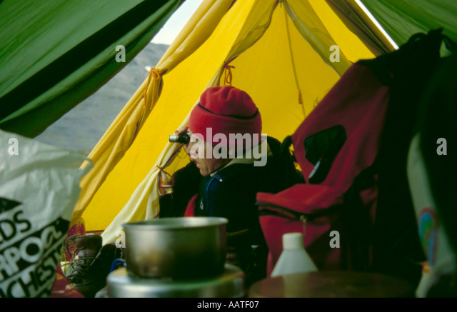 Man using a monocular whilst camping in the Ruotesvagge valley, Sarek National Park, Lappland, Norrbottens Län, - Stock Image