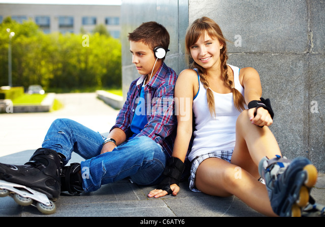 Couple of happy teens spending free time outside - Stock Image
