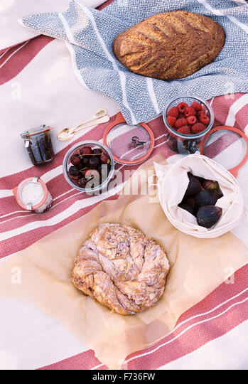 High angle view of food on a picnic blanket, breads and fruits. - Stock Image