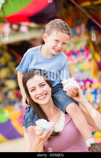 USA, Utah, Salt Lake City, Happy mother with son (4-5) in amusement park eating cotton candy - Stock Image