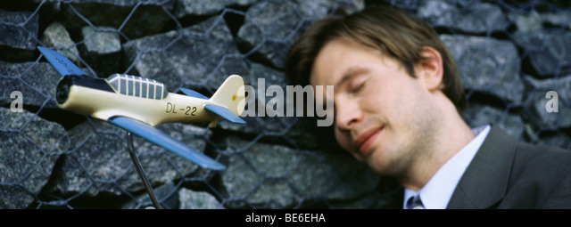 Man with eyes closed, smiling, leaning head against wall, toy airplane in foreground - Stock Image