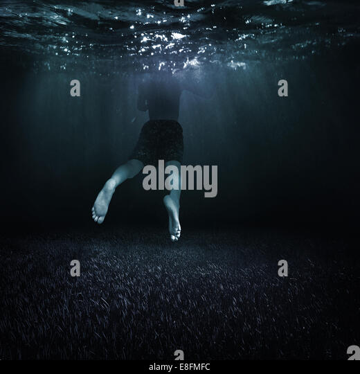 Canada, British Columbia, Vancouver, Boy (10-11) swimming in dark water - Stock Image