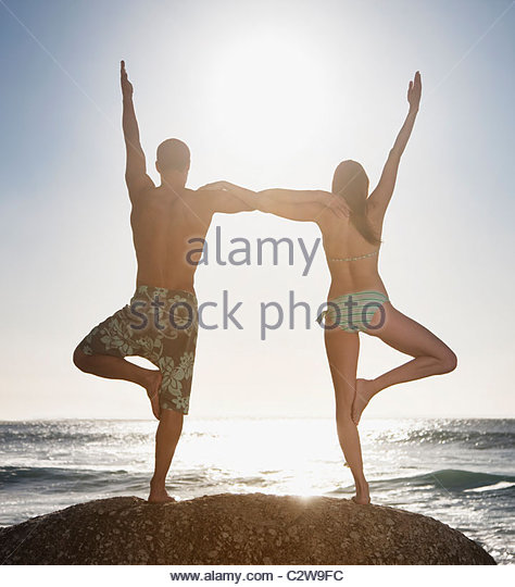 Couple balancing on one foot together at beach - Stock Image