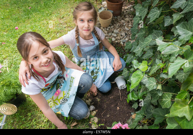 Two girls gardening, planting flowers together - Stock Image