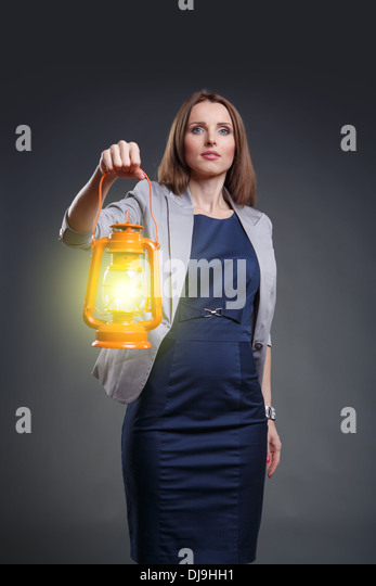 Studio portrait of a courageous and decided woman with the lantern - Stock Image