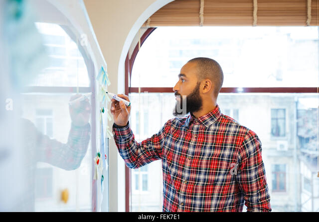Profile of handsome african man with beard standing and writing on whiteboard - Stock Image