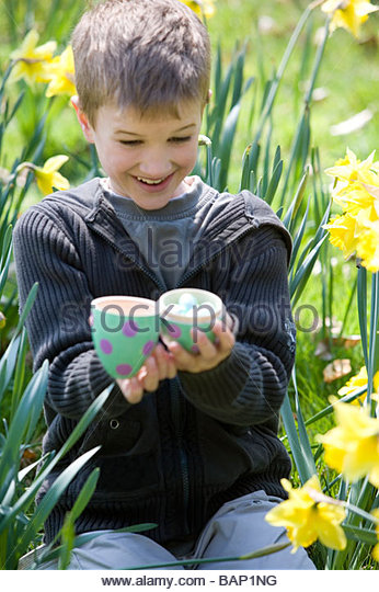 A young boy opening an Easter egg, smiling - Stock Image