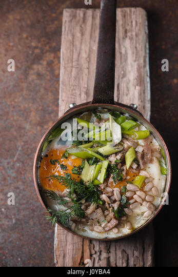 Fried eggs  with greens in the copper pot on the metal table  top view - Stock Image