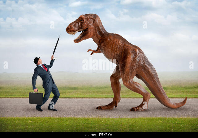 hostile business takeover concept businessman and tyrannosaurus dinosaur - Stock-Bilder