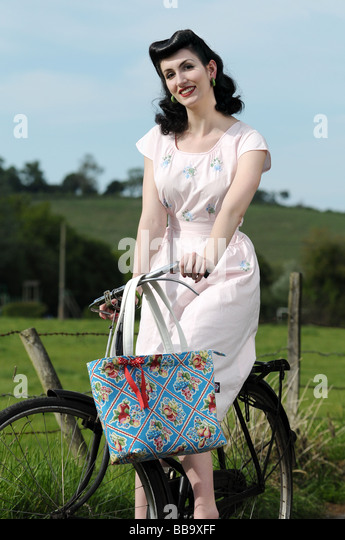 Woman wearing vintage clothing on an old bicycle - Stock-Bilder