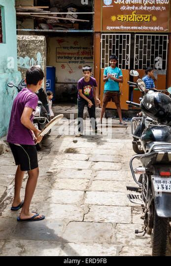 India Asian Mumbai Lower Parel Dhuru Wadi Sitaram Jadhav Marg boy friends playing cricket bat alley - Stock Image