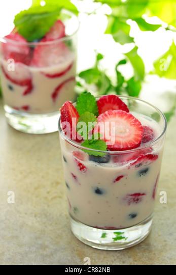 Vanilla yogurt with strawberries, blueberries and lemon balm - Stock Image