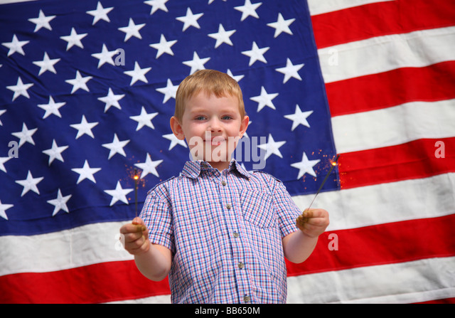 Young boy waving sparklers in front of American flag - Stock-Bilder