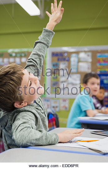 Enthusiastic elementary student with hand raised in classroom - Stock Image