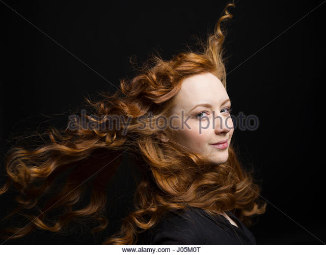 Portrait confident woman with wind blowing long curly red hair against black background - Stock Image