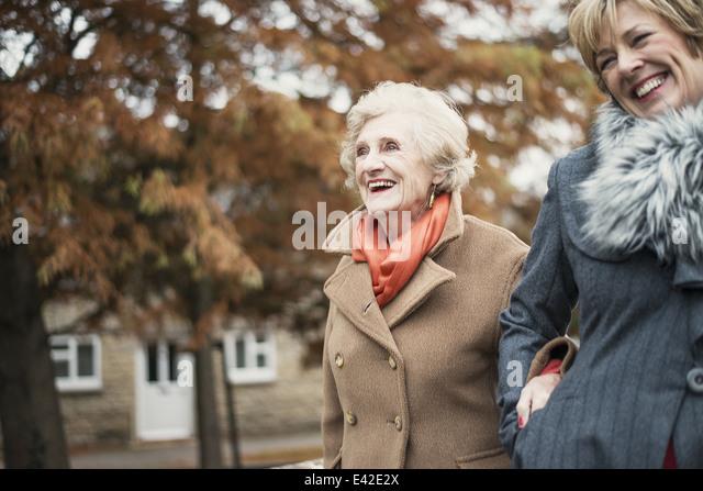 Senior woman and daughter walking outdoors - Stock Image