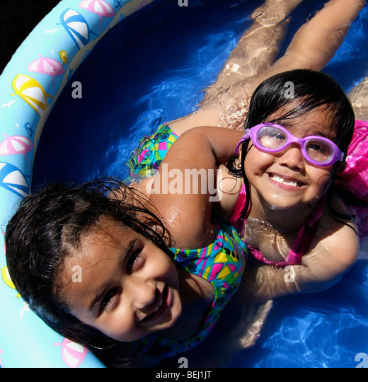 Two girls playing in home pool - Stock-Bilder
