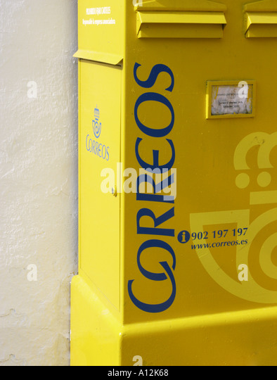 The vivid yellow of the postboxes for Correos the Spanish postal service is startling and cheerful - Stock Image