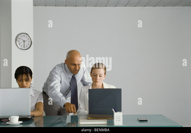 Professional man standing behind young female colleague, pointing at her computer screen - Stock Image