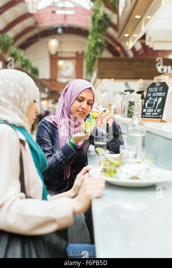 Woman reading label on bottle while having food with female friend at railroad station cafe - Stock Image