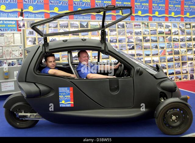 (dpa) - Torsten Eurich (L) and Klaus Kalkhof sit in their prototype vehicle called Sam, during an ecological fair - Stock Image