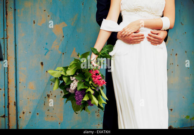 groom hugs his bride, medium close-up - Stock Image