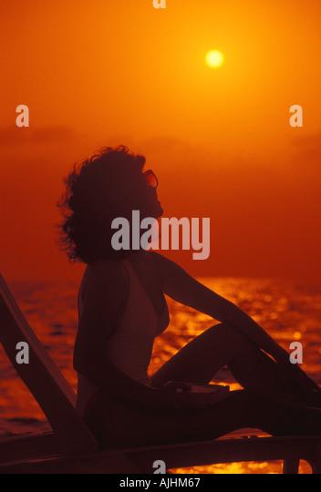 Beaches Woman on beach chair looking toward sun orange silhouette - Stock Image