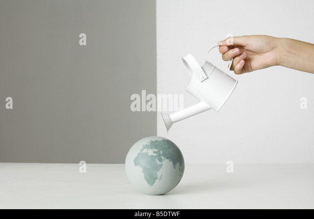 Hand holding watering can over small globe - Stock Image
