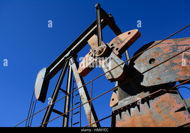 Rusty Oilfield Pumpjack (rocking horse) over a wellhead. Clear blue sky background. Illustrates oilfield life, petroleum - Stock Image