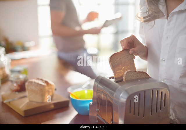 Woman putting bread in toaster - Stock Image