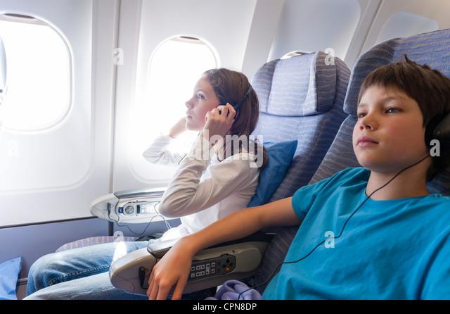 Children watching movie on airplane with headphones - Stock-Bilder