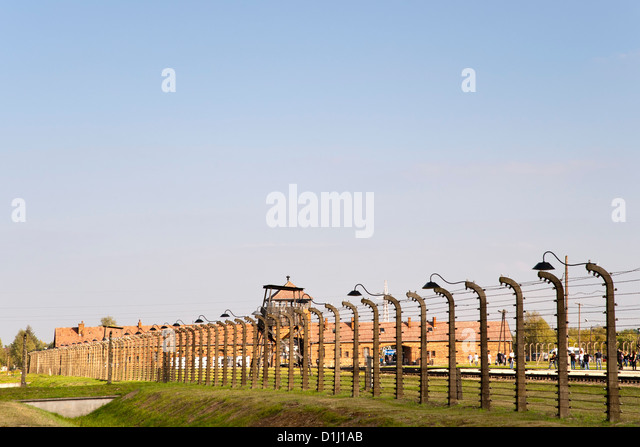 Electrified, barbed-wire fencing at the museum of the former Auschwitz II–Birkenau concentration camp in southern - Stock Image