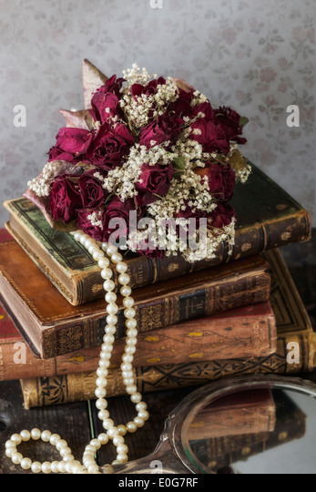 a dried rose bouquet on a pile of old books - Stock-Bilder