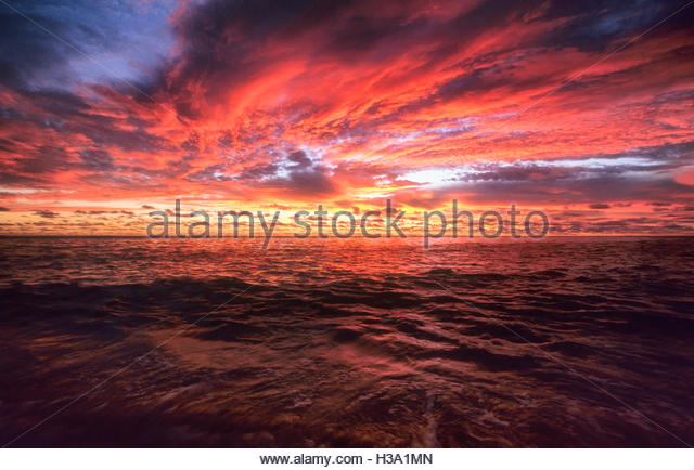 intense red sunset sky over the ocean - Stock Image