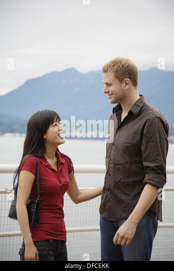A young man and woman laughing together, Vancouver, British Columbia, Canada - Stock Image